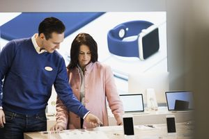 A woman talking to an employee in an electronics store.