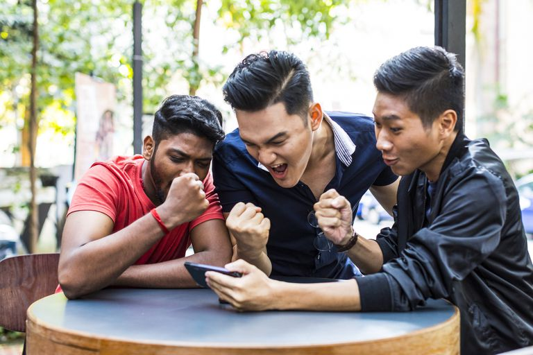 An image of three young men excitedly playing a game on a smartphone.