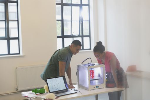 Two designers looking at a 3D printer