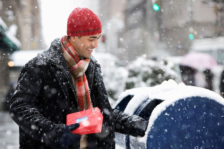 A man mailing holiday cards on a snowy day.