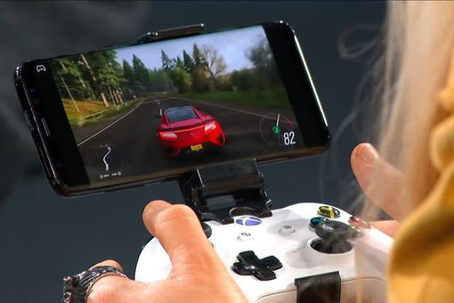 A person playing a game on a smartphone with an Xbox controller attached to it