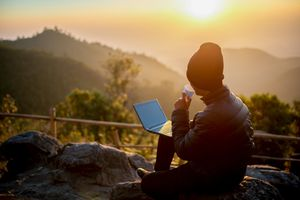 Hiker watching the sunrise with a laptop