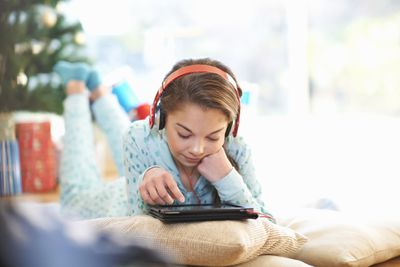 Child lying on living room floor looking at digital tablet at Christmas