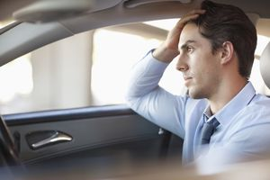 Man sitting in car with frustrated expression