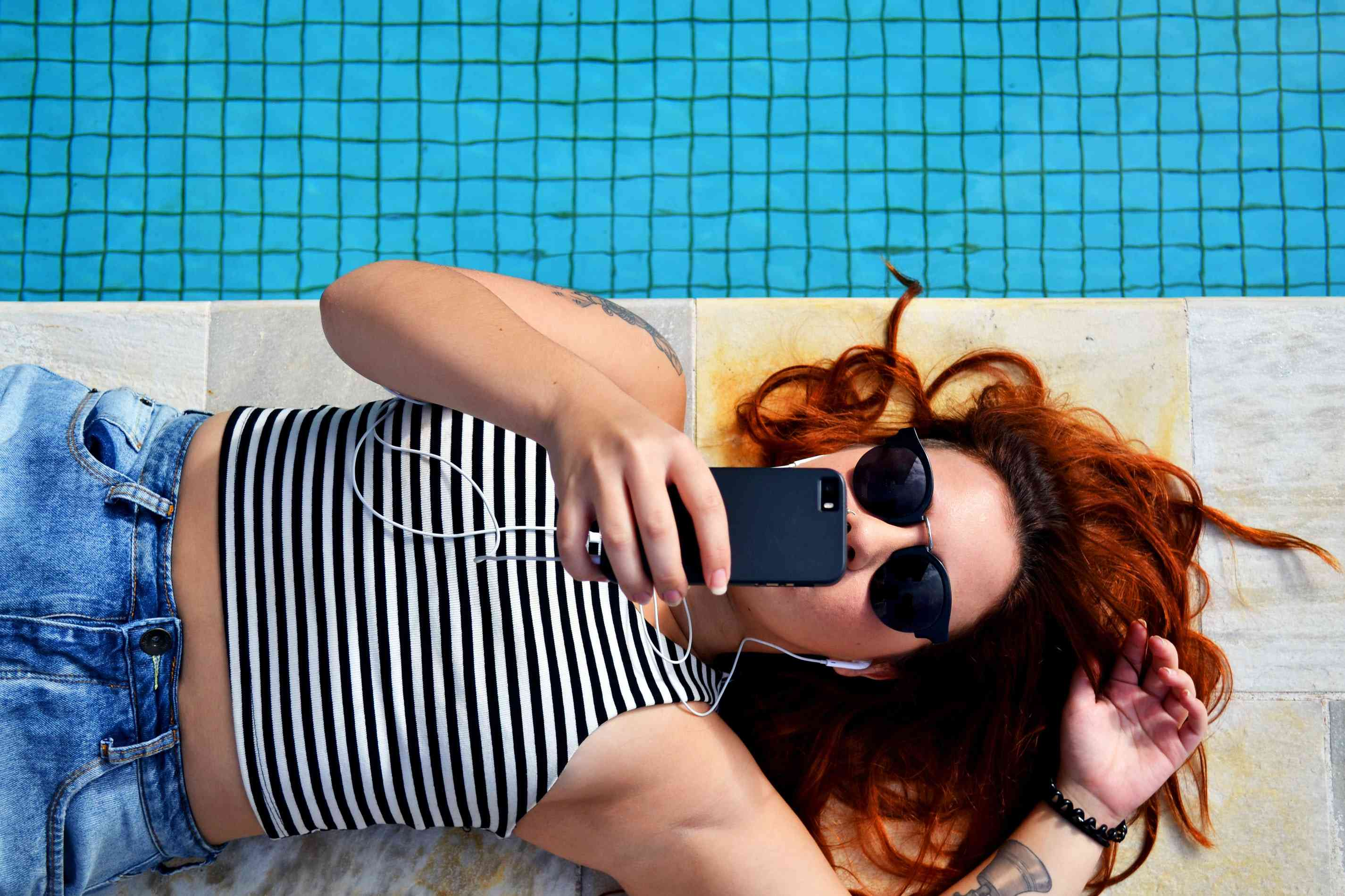 Woman lying next to a pool and listening to their phone