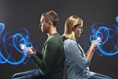 A man and woman using their smartphones with blue data swirls surrounding their hands.