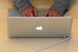 A customer types on a MacBook laptop at an Apple Store