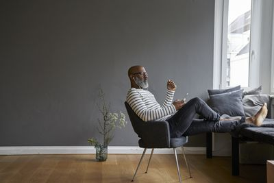 A man leaning back in a chair, using a smartphone