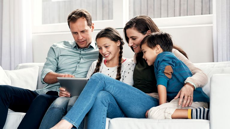 A father, mother, son, and daughter sitting on a sofa looking at data on an iPad.