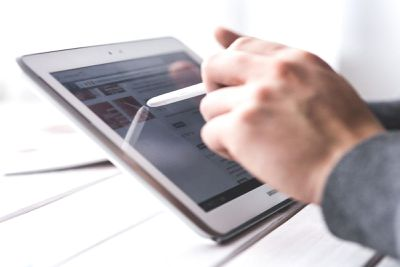 hand holding Apple Pencil against an iPad screen