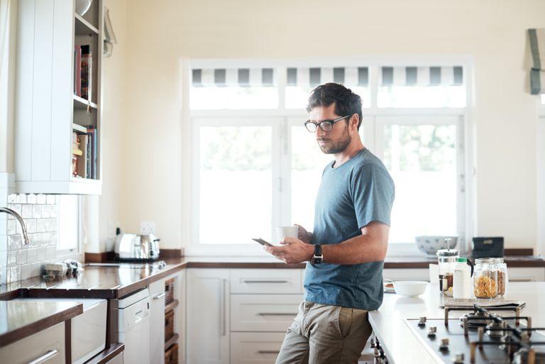 man in kitchen reading phone