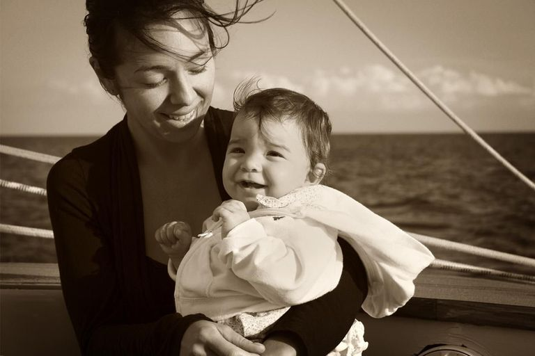 Mother and smiling baby on boat; sepia tone
