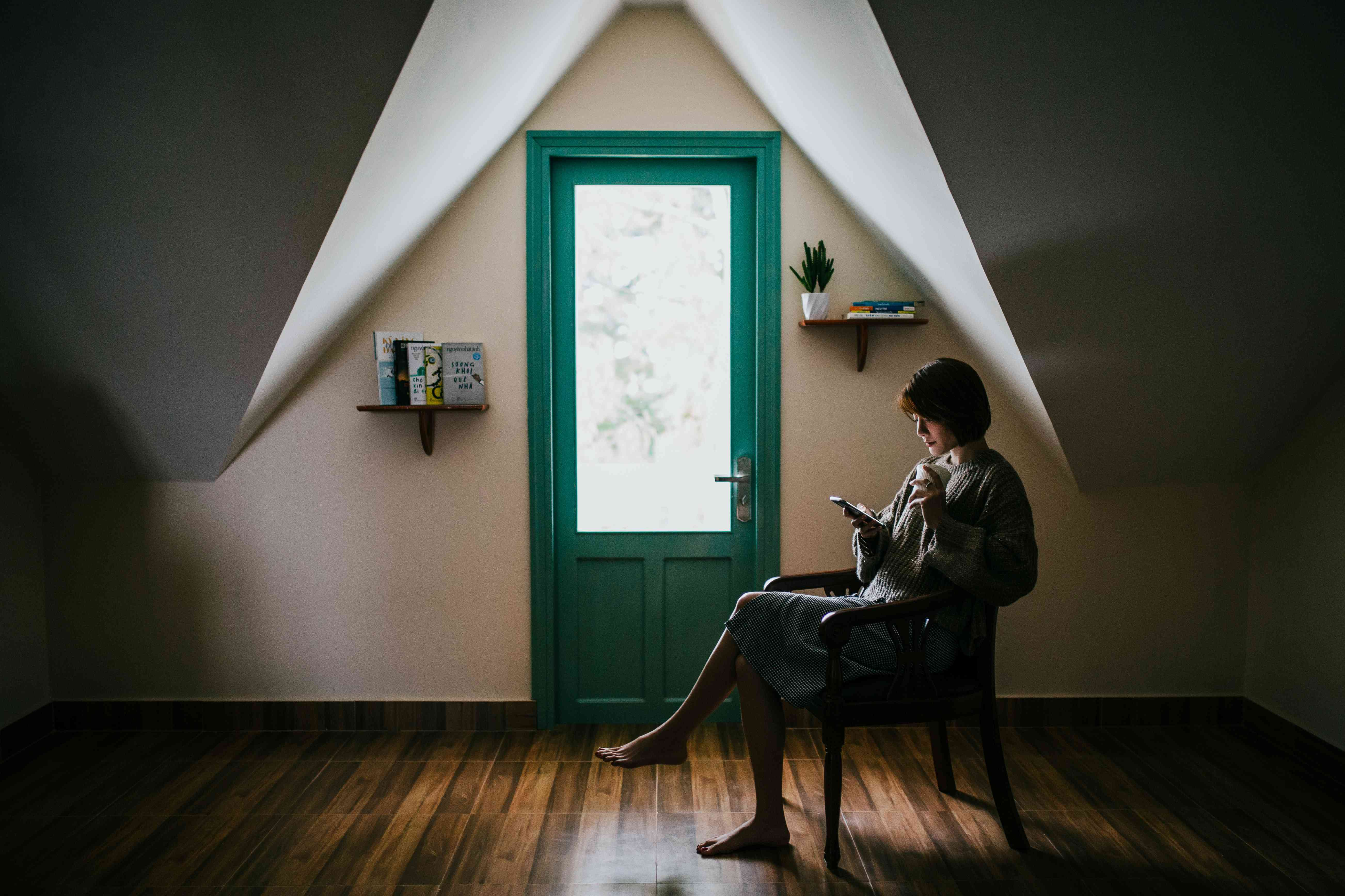Someone sitting on a chair in an empty room, reading on an e-book reader.