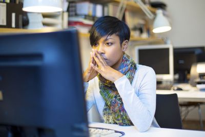 Young woman concentrates on her work in front of computer