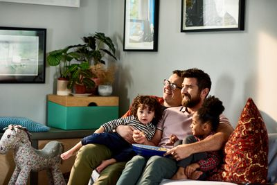 Family with young children watching TV together.