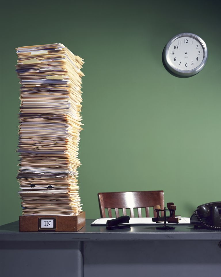 Stack of paperwork in inbox and clock with no hands
