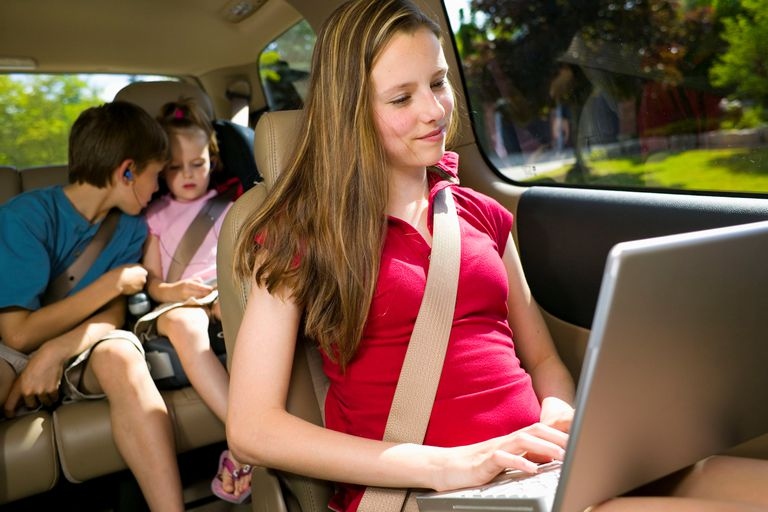 Young woman in a car using a laptop with children strapped into their seats behind her