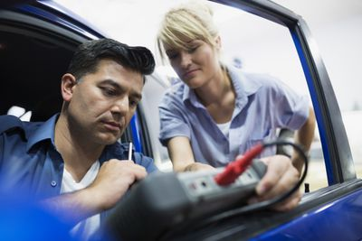 Two people looking at a car scan tool