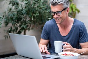 Man wearing glasses using an internet browser on his laptop in a cafe.