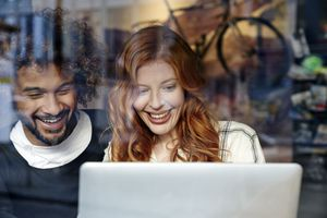 Photo through a window of man and woman laughing at computer