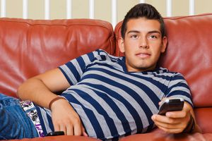 A college student watching TV in a dorm room