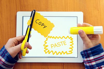 Scissors cutting paper that says copy, tablet says paste.