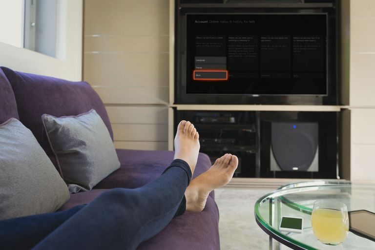 A woman's feet on the couch with the TV is being set to appear offline on Xbox One