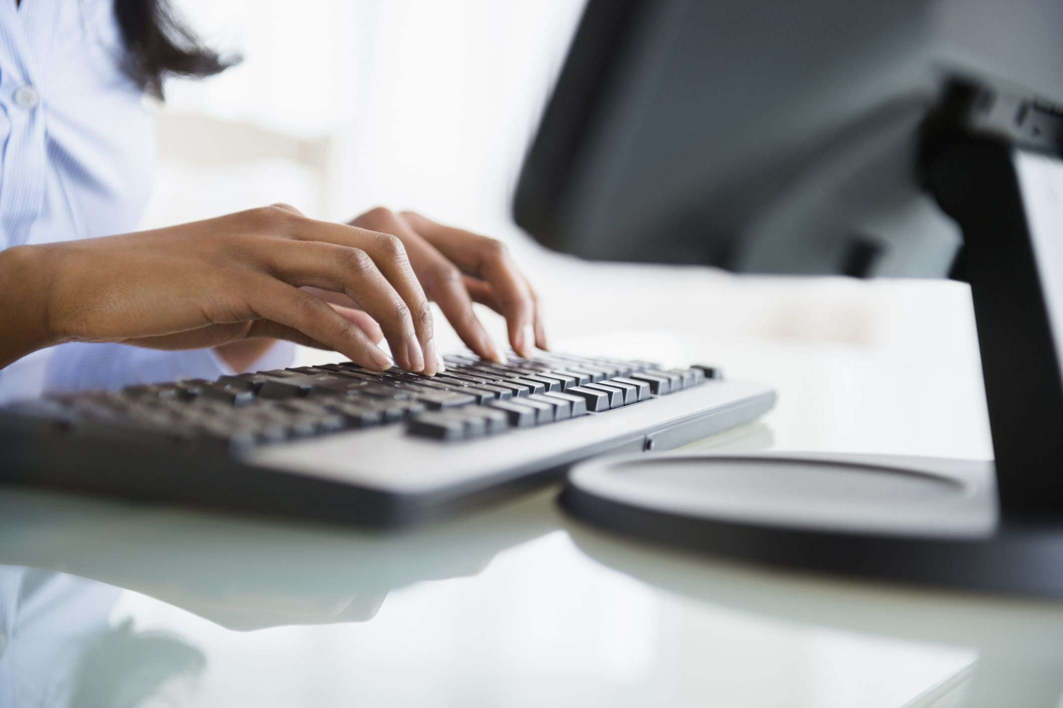 A woman using a keyboard at a desk.