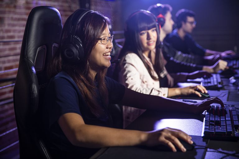 A girl sits at a PC streaming gameplay.