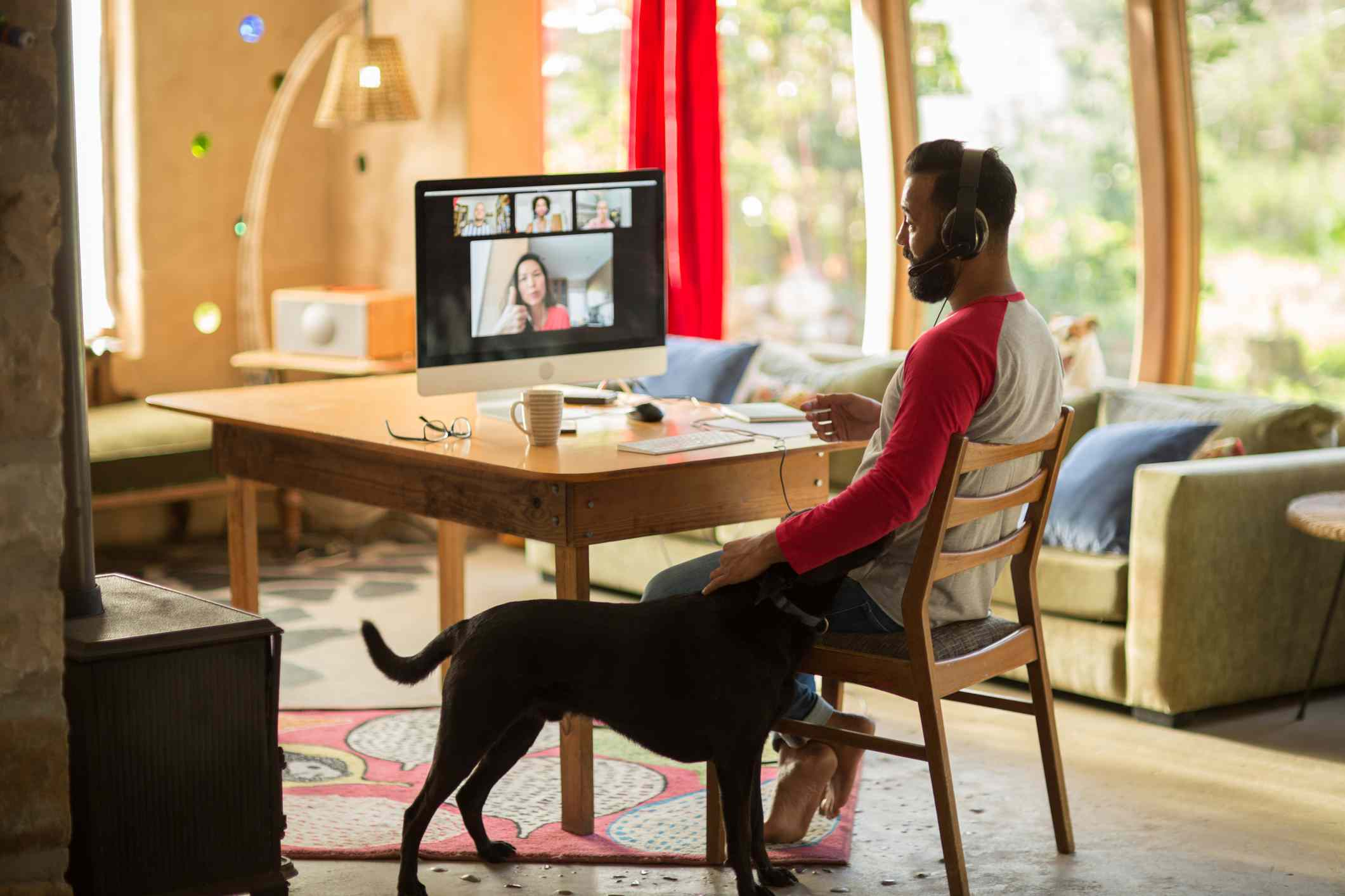 Man working from home on his computer and petting his dog during lockdown