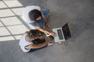Two people using a MacBook computer sitting on the ground.