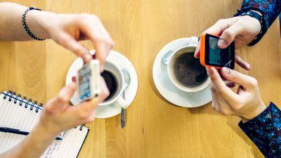 Two people in a cafe sending a peer-to-peer money exchange via their iPhone smartphones