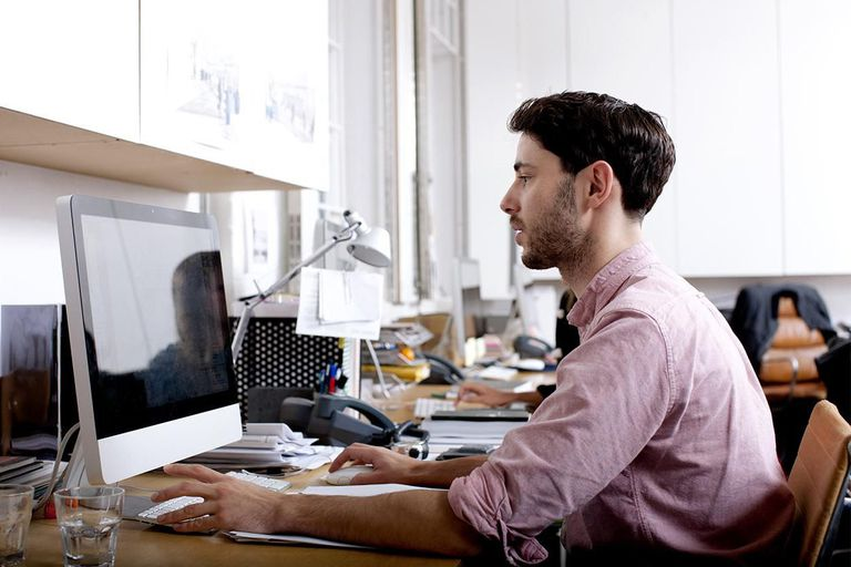 Man in light red shirt working on a desktop computer at a desk