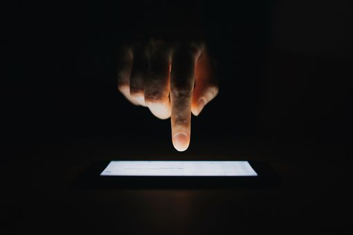 A hand using a smartphone in the dark.