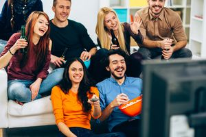 Group of people watching TV and having fun