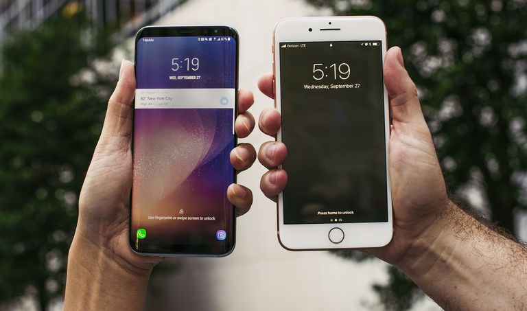 Android phone and iPhone held side-by-side