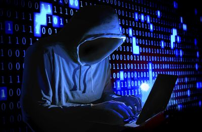 Figure wearing a hood typing on a computer