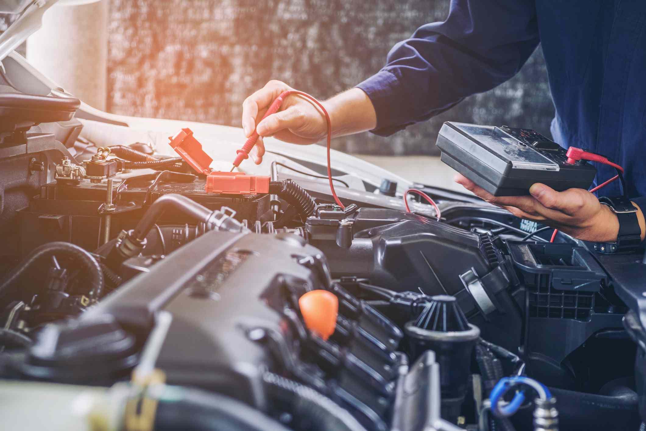 A car mechanic diagnosing a car engine.