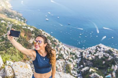 Traveller taking a selfie on top of a cliff face