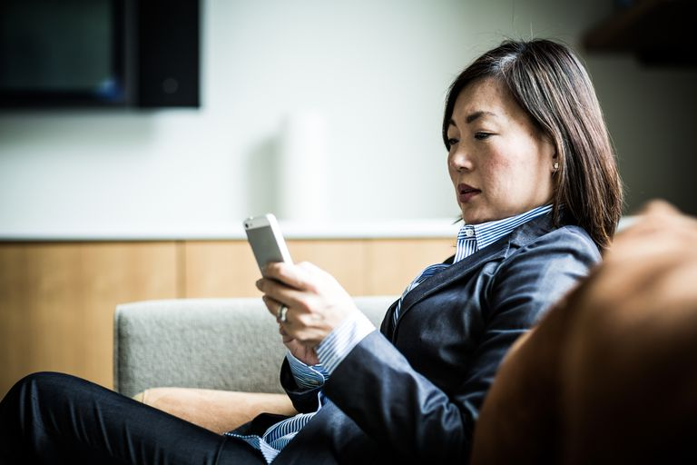 Businesswoman sitting on a couch looking at her iPhone