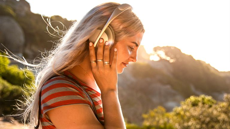 Woman wearing Bose Headphones 700 Silver Bluetooth headset.