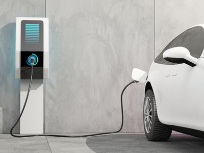 A white EV connected to a charging station.