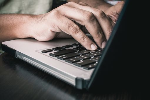 A man typing on a Macbook laptop