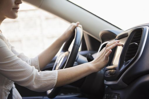 A woman sitting in the driver's seat of a car, tapping on a navigational screen on the dashboard