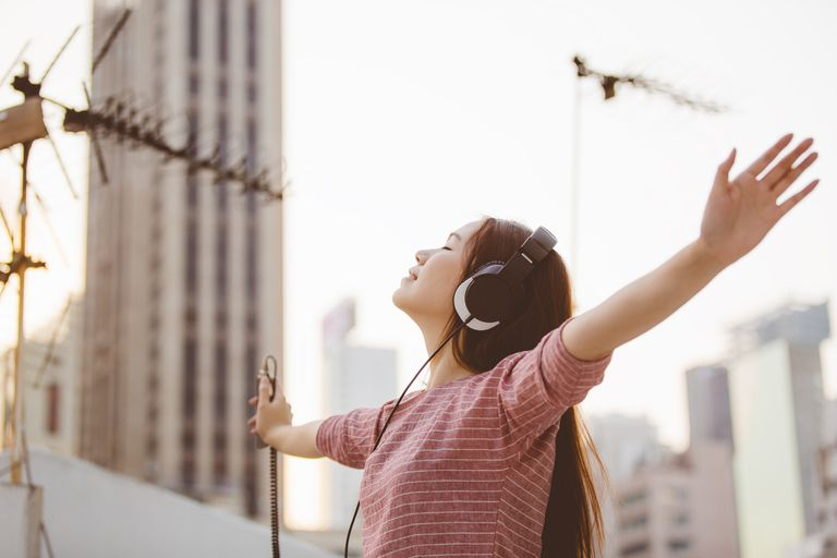 Woman listening to music on phone through headphones with hands in the air