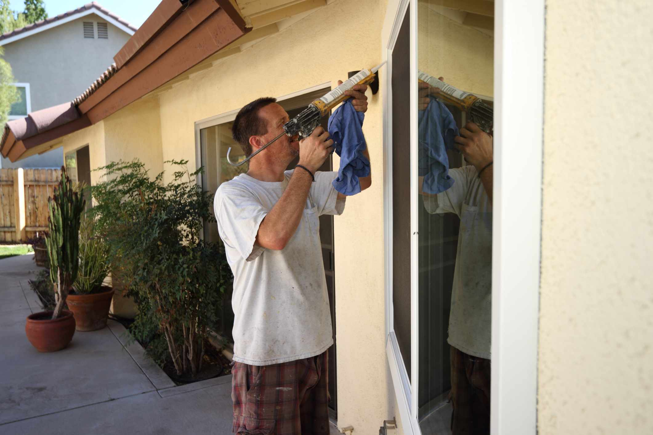 Homeowner using a caulking gun outside