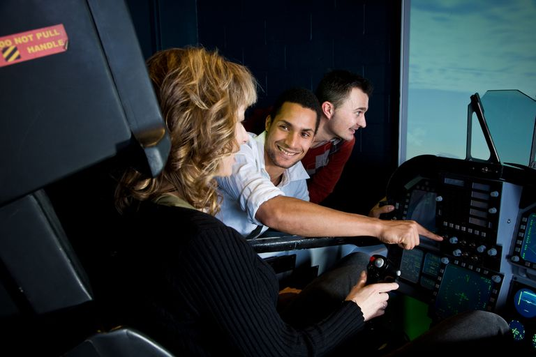 A group of people in a flight simulator.