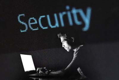 Programmer using computer in front of the word Security digitally projected behind them