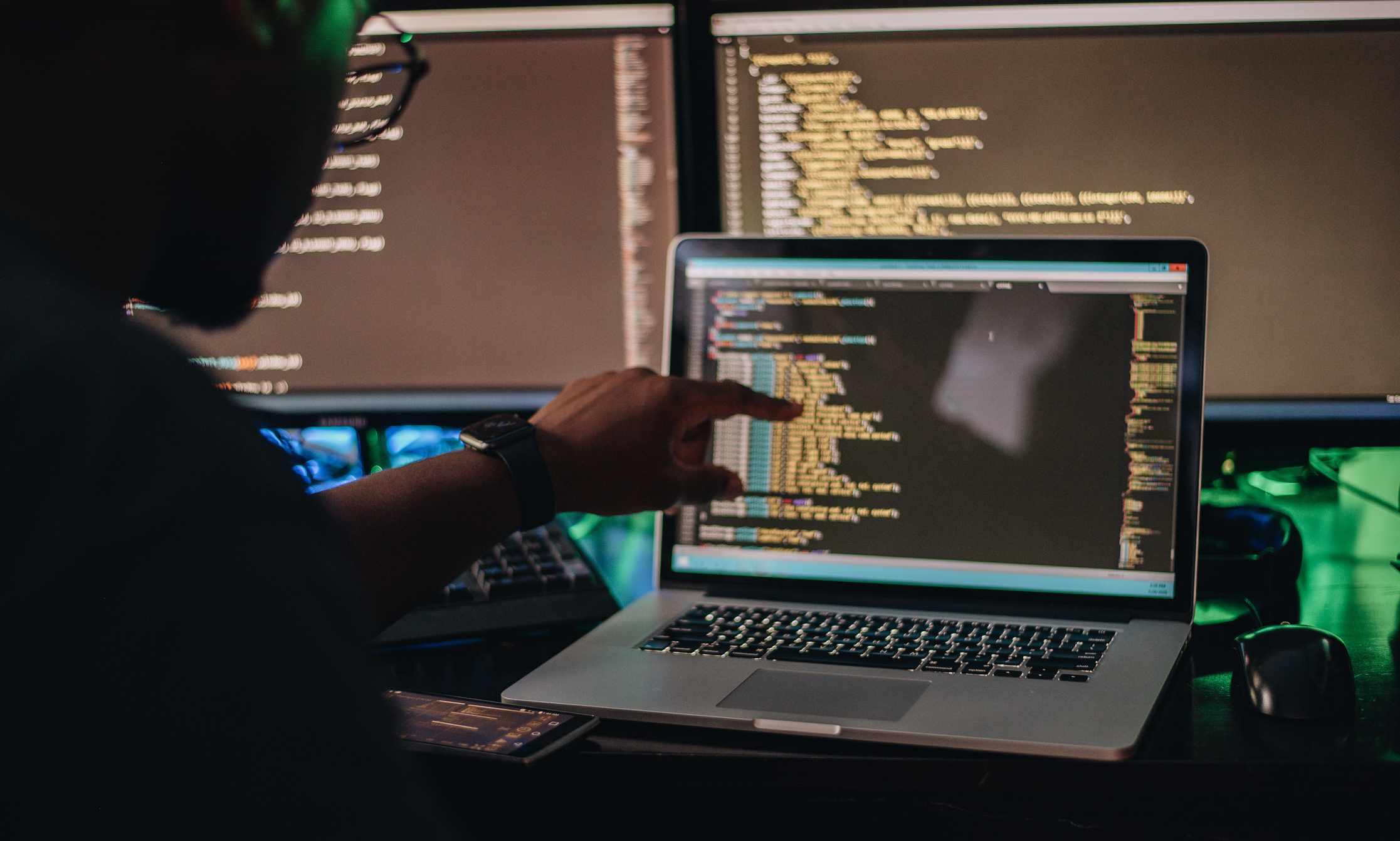 A man codes on a laptop