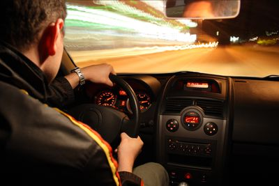 Man driving car fast at night, picture taken with long exposure of interior of car man driving